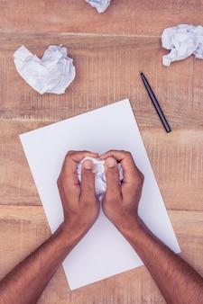 Imagem recortada de empresário fazendo bolas de papel na mesa no escritório