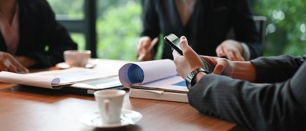Imagem recortada de empresários trabalhando juntos na mesa de reunião.