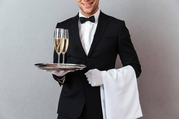 Imagem recortada de garçom segurando copos de champanhe e toalha.