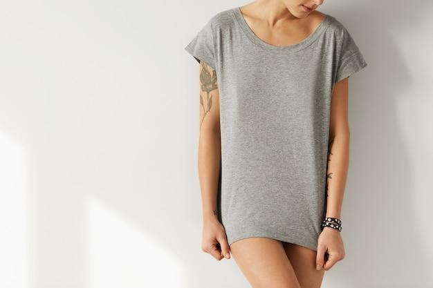 Imagem recortada de hipster feminino com corpo perfeito, vestindo camiseta oversize cinza, posando como modelo para a coleção de moda
