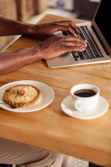 Imagem recortada de homem casual usando laptop