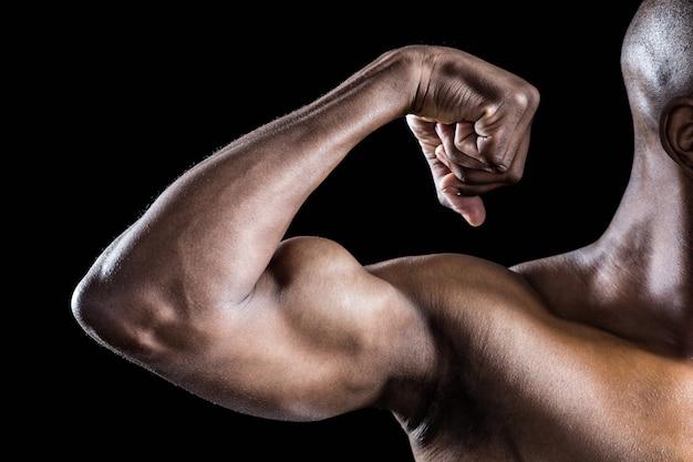 Imagem recortada de homem musculoso flexionando os músculos