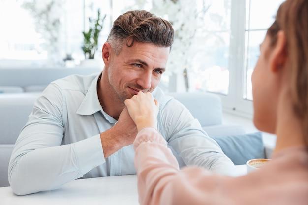 Imagem recortada de homem sorridente na camisa, sentado junto à mesa