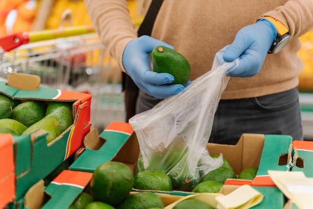 Imagem recortada de homem usa luvas médicas de proteção em borracha e compra abacate no supermercado
