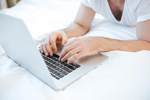 Imagem recortada de homem usando laptop deitado na cama