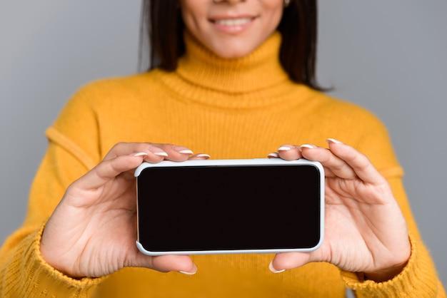 Imagem recortada de incrível mulher animada posando isolada sobre uma parede cinza, mostrando o visor do telefone móvel.