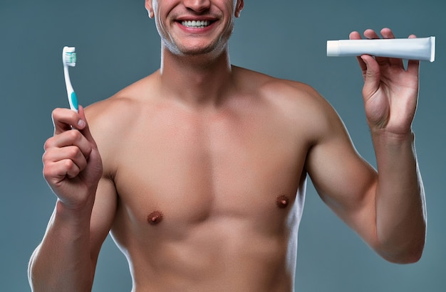 Imagem recortada de jovem bonito isolado. retrato de homem musculoso sem camisa está de pé sobre um fundo cinza com escova e pasta de dentes na mão. conceito de cuidados de homens.