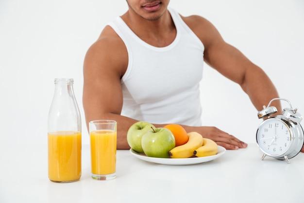 Imagem recortada de jovem desportista perto de frutas.