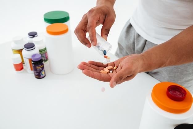 Imagem recortada de jovem desportista segurando vitaminas e comprimidos de esporte.