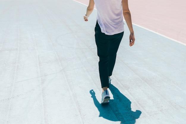 Imagem recortada de jovem em esportes calças, t-shirt e tênis andando em um campo de esportes