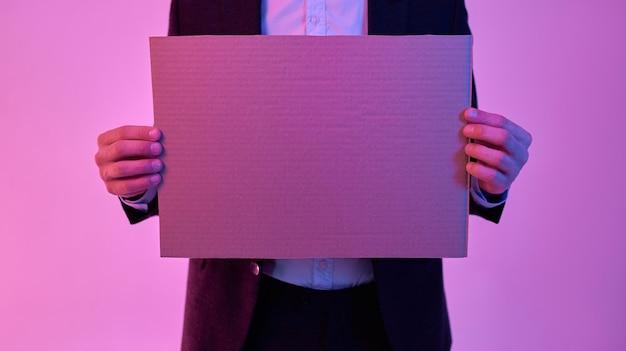 Imagem recortada de jovem empresário atraente de terno preto e camisa branca segurando um papelão nas mãos com um espaço vazio para o texto isolado em neon rosa