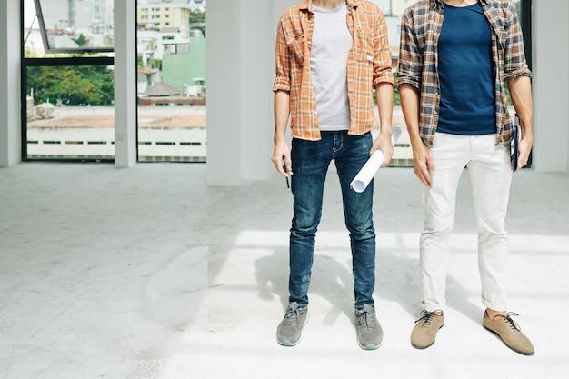 Imagem recortada de jovens engenheiros com planta e computador tablet dentro de um prédio em construção