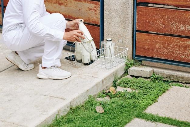Imagem recortada de leiteiro trocando garrafas de vidro vazias por outras cheias de leite na porta de entrada dos clientes