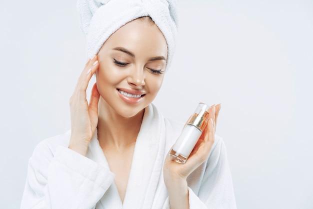 Imagem recortada de linda mulher charmosa toca suavemente sua pele lisa, usa produto cosmético para cuidar do corpo, aplica hidratante após o banho. cosmetologia natural, conceito de tratamento facial