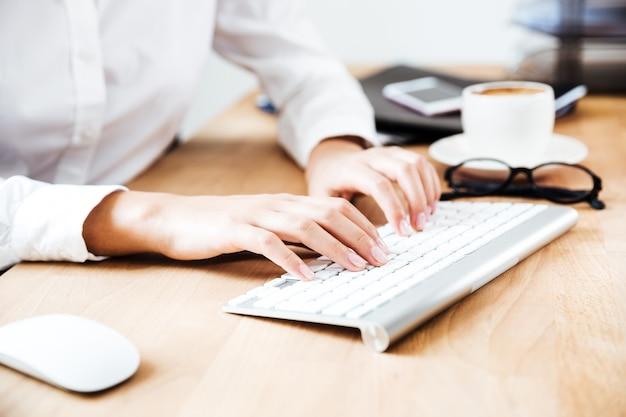 Imagem recortada de mãos femininas digitando no teclado no escritório