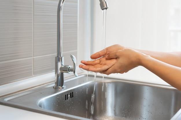 Imagem recortada de mulher asiática lavando as mãos na pia antes de cozinhar na cozinha de casa.