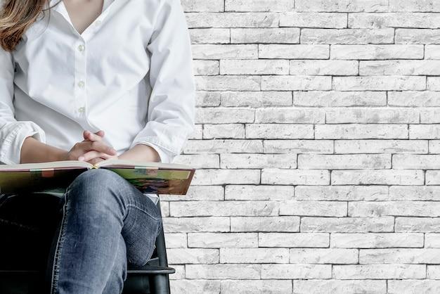 Imagem recortada de mulher com livro sentado na cadeira com parede de tijolos antigos