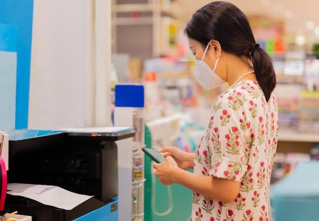 Imagem recortada de mulher com máscara protetora segurando telefone celular com impressora para imprimir o documento