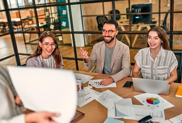 Imagem recortada de mulher de negócios, mostrando o gráfico em papel para um grupo de colegas sentados à mesa com laptops em um escritório moderno.