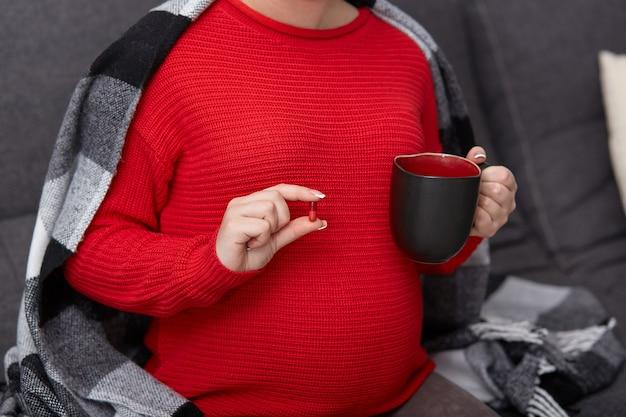 Imagem recortada de mulher grávida toma droga, segura caneca com chá, bebe remédio durante a gravidez, precisa de vitaminas