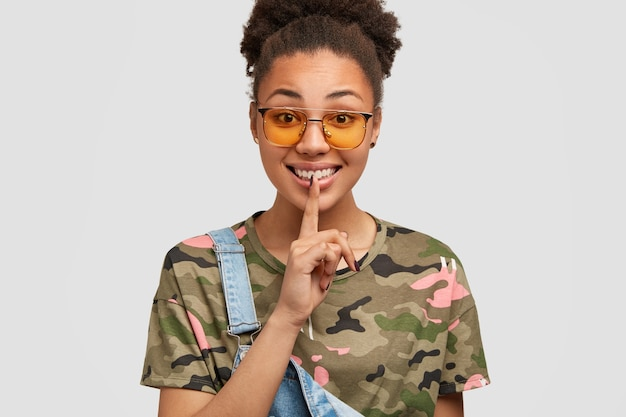 Imagem recortada de mulher morena satisfeita com os dedos indicadores nos lábios, de bom humor, conta o segredo para o melhor amigo