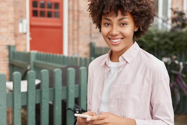 Imagem recortada de mulher negra com corte de cabelo afro, usa celular, satisfeita, posa ao ar livre em setor privado perto de sua casa,