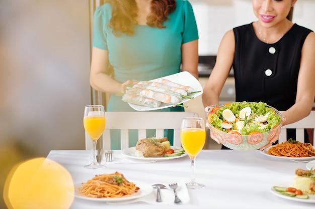 Imagem recortada de mulheres colocando uma tigela de salada de legumes e um prato com rolinhos primavera na mesa de jantar