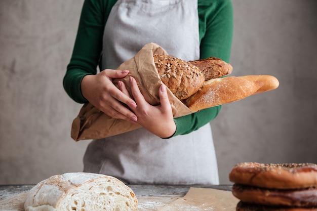 Imagem recortada de padeiro feminino segurando o saco com pão
