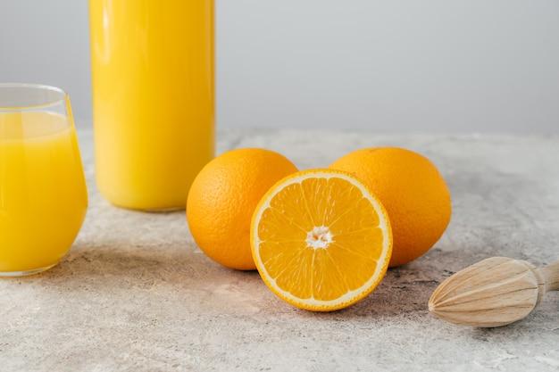 Imagem recortada de suco de laranja em vidro, três laranjas maduras e espremedor de frutas de madeira