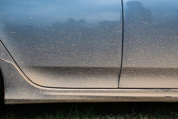 Imagem recortada de um carro enlameado na porta lateral