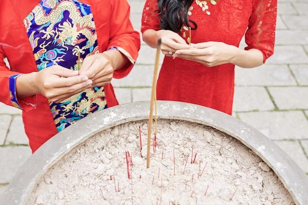 Imagem recortada de um casal vestido de vermelho com incensos nas mãos, rezando em uma antiga urna de bronze no templo budista