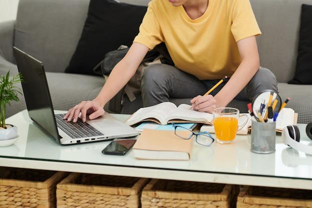 Imagem recortada de um estudante fazendo lição de casa em casa, ele está verificando o artigo na tela do laptop e sublinhando frases no livro dos alunos