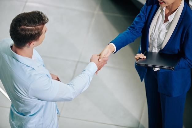 Imagem recortada de um gerente de vendas sorridente, apertando a mão do cliente ao cumprimentá-lo na concessionária de automóveis