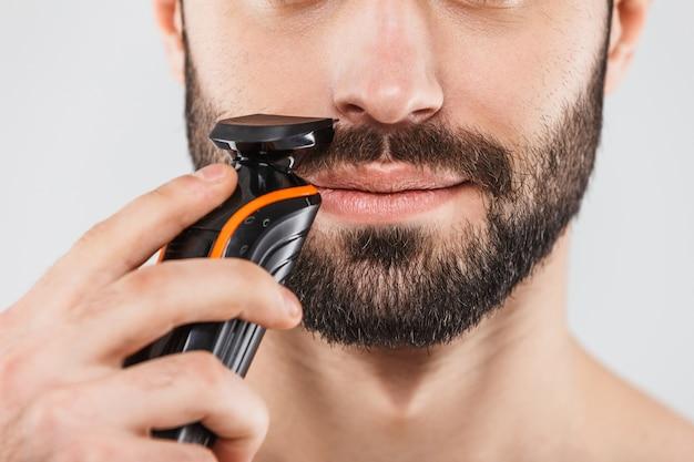 Imagem recortada de um homem barbudo bonito fazendo a barba com um barbeador elétrico isolado sobre o branco