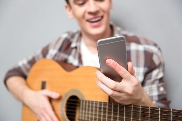 Imagem recortada de um homem com guitarra usando o smartphone. foco no smartphone