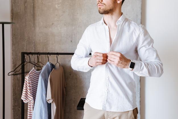 Imagem recortada de um homem de camisa branca se abotoando