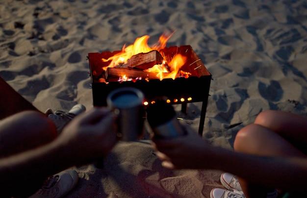 Imagem recortada de um homem e uma mulher segurando canecas de chá perto do fogo, em uma praia à beira-mar.