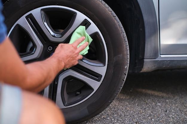 Imagem recortada de um homem irreconhecível limpando a roda de um carro com um pano ao ar livre