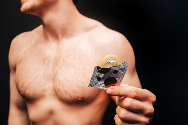 Imagem recortada de um homem segurando um pacote aberto com um preservativo na mão. rosto obscuro de cara musculoso sexual com torso desportivo nu. conceito de proteção sexual. isolado em fundo escuro. sessão de estúdio