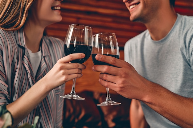 Imagem recortada de um jovem casal no quarto com taças de vinho