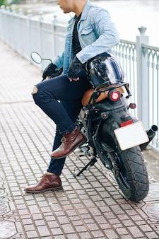 Imagem recortada de um jovem descolado com botas de couro e jaqueta jeans apoiado em sua motocicleta ao ar livre