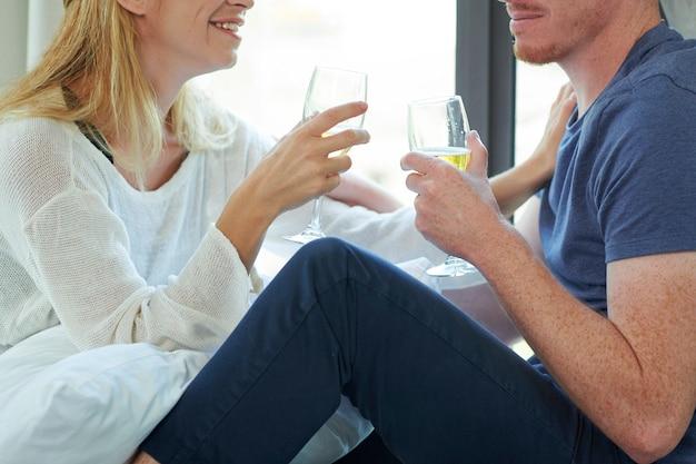 Imagem recortada de um jovem e uma mulher bebendo champanhe e discutindo notícias sentados no parapeito da janela