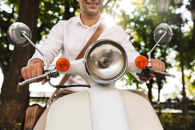 Imagem recortada de um jovem empresário sentado em uma motocicleta ao ar livre