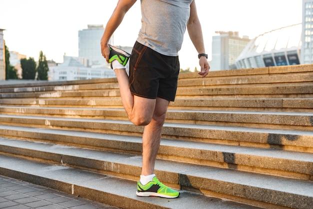 Imagem recortada de um jovem esportista esticando as pernas