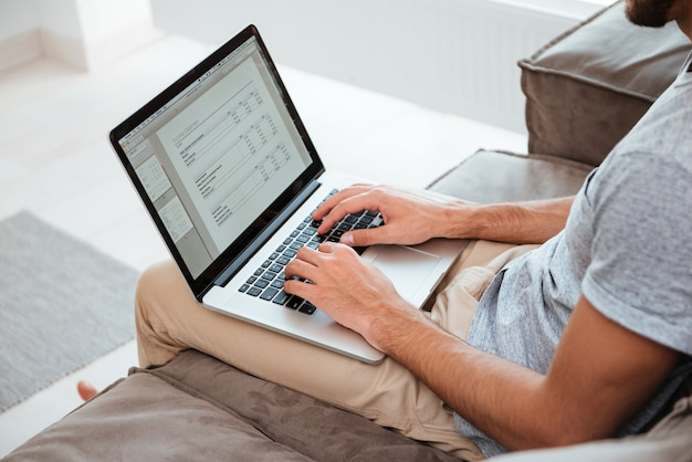 Imagem recortada de um jovem que trabalha em seu laptop enquanto está sentado no sofá.