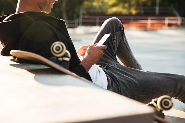 Imagem recortada de um skatista sorridente, olhando para o telefone móvel
