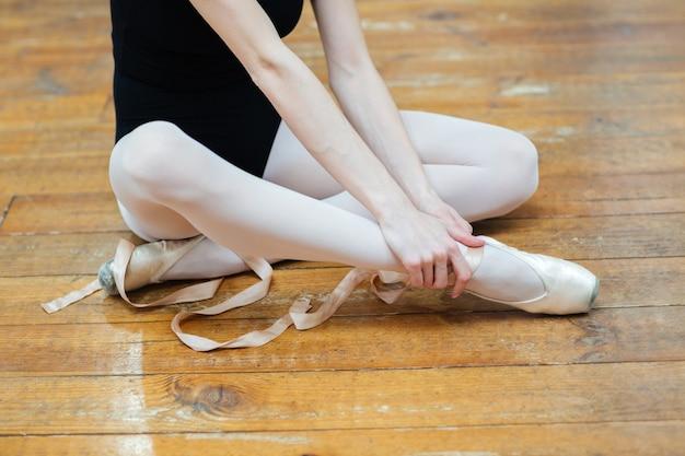 Imagem recortada de uma bailarina em pontas com dor no tornozelo