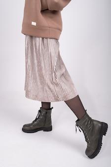 Imagem recortada de uma jovem com capuz e saia plissada