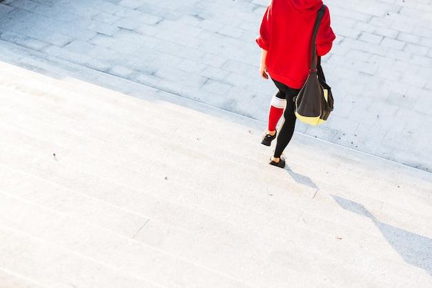Imagem recortada de uma jovem desportista com um moletom, caminhando ao ar livre, carregando uma sacola esportiva