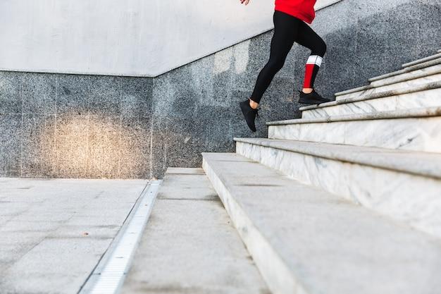 Imagem recortada de uma jovem desportista subindo as escadas ao ar livre